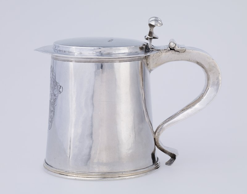 Tankard, Charles II, slightly tapering cylindrical body, engraved with contemporary armorials within a plume cartouche; cap-shaped cover; bifurcated thumbpiece and simple scroll handle, on moulded base.