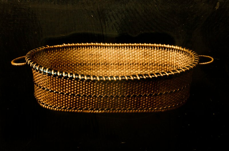 Shallow oval basket with handles in wrapped twined and plain weave. Only design consists of three black raised bands and a black rim. Colors are brown and black.