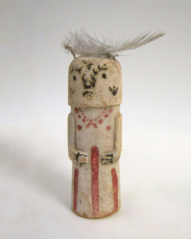 Hopi ceremonial doll, painted; white with red necklace and red bands on skirt; dome shaped head, emerging direct from shoulders, with painted face and one chicken feather above left ear; twentieth century