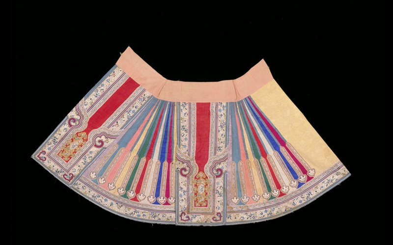 Skirt made up of gored sides of colored silks of cloud pattern, each bordered with a strip of peacock blue satin and having a band of white, flowered braid terminating in fungus form on lower third of skirt. Main panels of red silk with cloud pattern, and an applique design of a sage and symbols embroidered in couched gold threads and satin stitch in colors. Main panels have elaborate shaped borders of blue satin, white satin embroidered with flowers, and symbols in colored silks; narrow, striped satin ribbon, and white silk braid with pattern of stylized flowers in colors. The same four borders trim the bottom of the skirt; lining of badly faded red-rose silk.