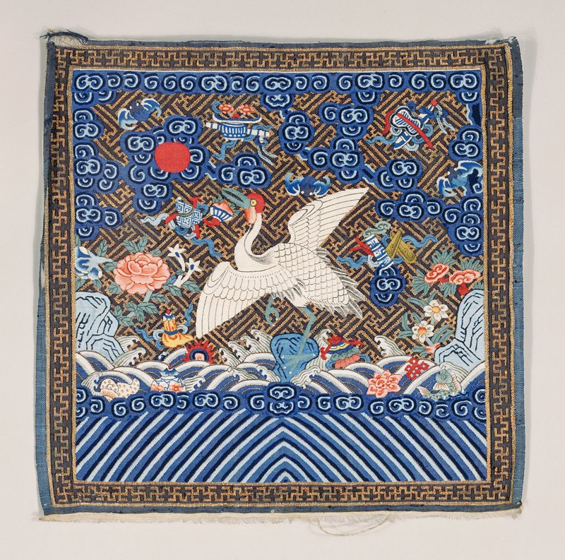 Mandarin Square of blue k'ossu with white crane design. Swastika fret diaper in gold, clouds, peonies, Buddhist symbols, sun, eternal sea. Border of swastika meander in gold. Unlined.