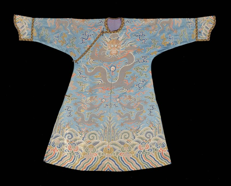 Concubine robe similar to 42.8.1, but of blue satin brocaded in blue, green, yellow, shades of rose and gold. Border design of same pattern but with paler colors. Neckline and cuffs bordered with narrow band of black and gold brocade. Lining of thin blue silk. This robe not slit at bottom front and back.