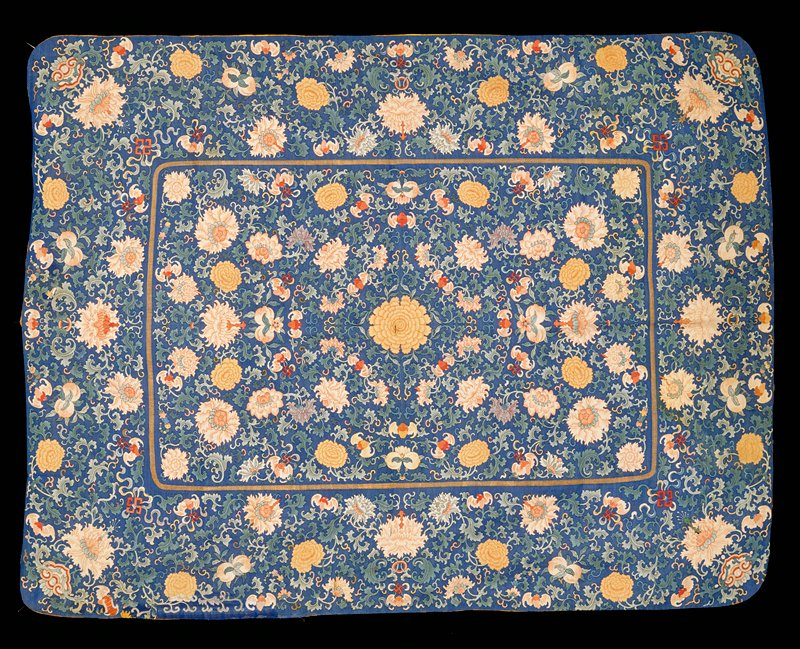 Throne seat cover of blue k'ossu with the same floral and emblem design as 42.8.238, except for double peach here seen in panel. Central panel oblong instead of shaped; border wider and no boxed border. Painted details. Lining of yellow satin with cloud pattern. Inscription on back.