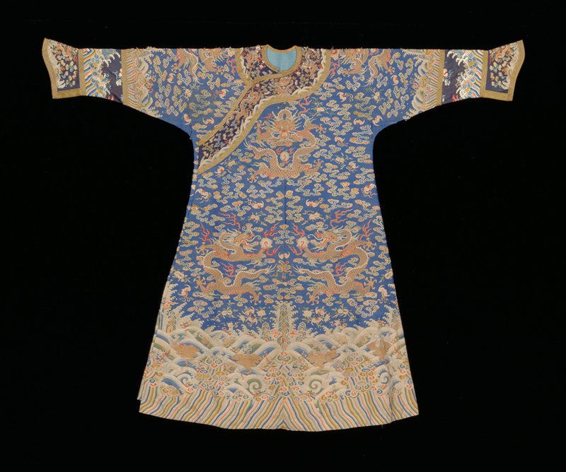 Imperial 12-symbol robe of Kangxi blue kesiwith nine 5-clawed dragons in gold, those in profile grasping the Heavenly Jewel. Scattered through ground are loose cloud forms, bats, the double peach, swastika, and sprays of flowers. On this robe the twelve symbols, with exception of the sun, moon, constellation, and mountains, appear ont he border, which is formed of a rather narrow area of slanting wavy stripes with rolly waves, clouds, and Buddhist and Daoist symbols. A similar border in miniature at elbows where sleeves continue with a wide band of wave and earthe designs embroidered on poor quality blue sild, and end in an embroidered cuff edged all around with band of modern gold and black brocade. Collar and front band of dark blue kesi edged with same gold and black brocade. The disposition of the twelve ancient symbols is thought to indicate an early practice. On front border appear the phoenix, dragons, and the cups; dragons, phoenix, and cups with some painting. On back border are the fire, water, weed, millet, the axe. Coat slit at sides and lined with thin blue silk. Kesi worn and patched. Color appears faded in spots, but may be soiled.