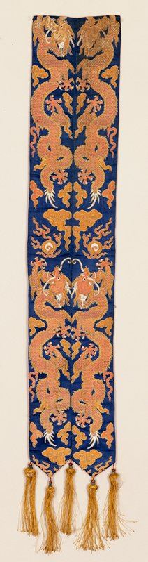 Pair of Small banners sewn together. Blue satin brocade with four rampant five-clawed dragons in rose and tan. Scattered, loose clouds and the Heavenly Jewel in the same colors. Lining of thin rust-colored silk, fringed end.