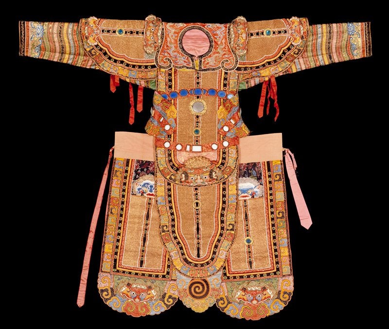 Theatrical robe for a warrior, the heavy gold thread panels, body section, and epaulets representing the chain armor of a warrior. Yoke of rust-red satin embroidered with five-clawed dragons in couched gold thread. Tiger claw borders of colored brocades, wavy jewel, stone and metal bosses on velvet border bands throughout. Sleeves of green satin banded with wavy strips of gold and colored brocades. Skirt composed of five shaped panels. Linig of pink satin. Seal inscription in front.