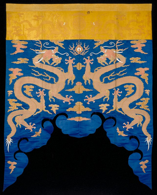Shaped hanging - Altar Frontal? in dark blue satin brocade. Two enormous rampant five-clawed dragons in rose and tan in a field sparsely scattered with loose clouds in the same color. Lower edge shaped in a scrolled edge, the two sides dipping into long ends from the middle portion, which is shaped like a scpetre-head. Upper border of monotone gold-colored satin brocade with two five-clawed dragons flanking a long-life character. Loose clouds scattered in surrounding area. Linings of blue and yellow cotton. Traces of an inscription on yellow cotton band of upper border.