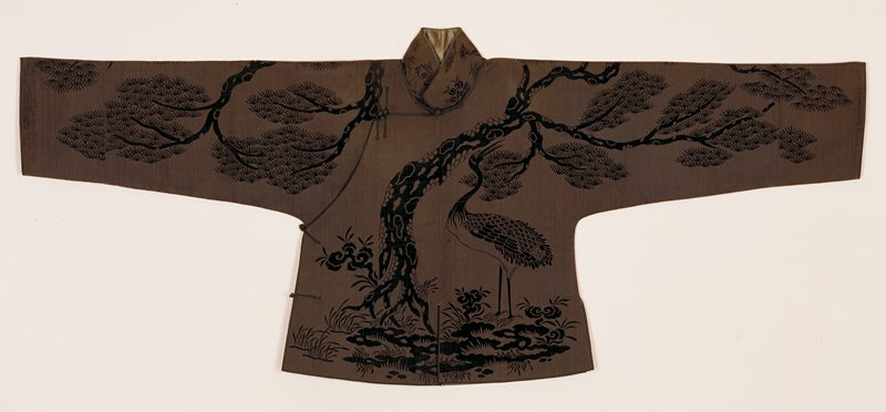 Short jacket of taupe cut velvet on taupe ribbed gound. The design includes a crane, branching pine trees, spotted deer and the fungus; all symbols of longevity. Standing collar, bound with black satin. Medium wide sleeves and edges also bound with balck satin. Note two patch pockets on under flap of front. A woman's jacket.