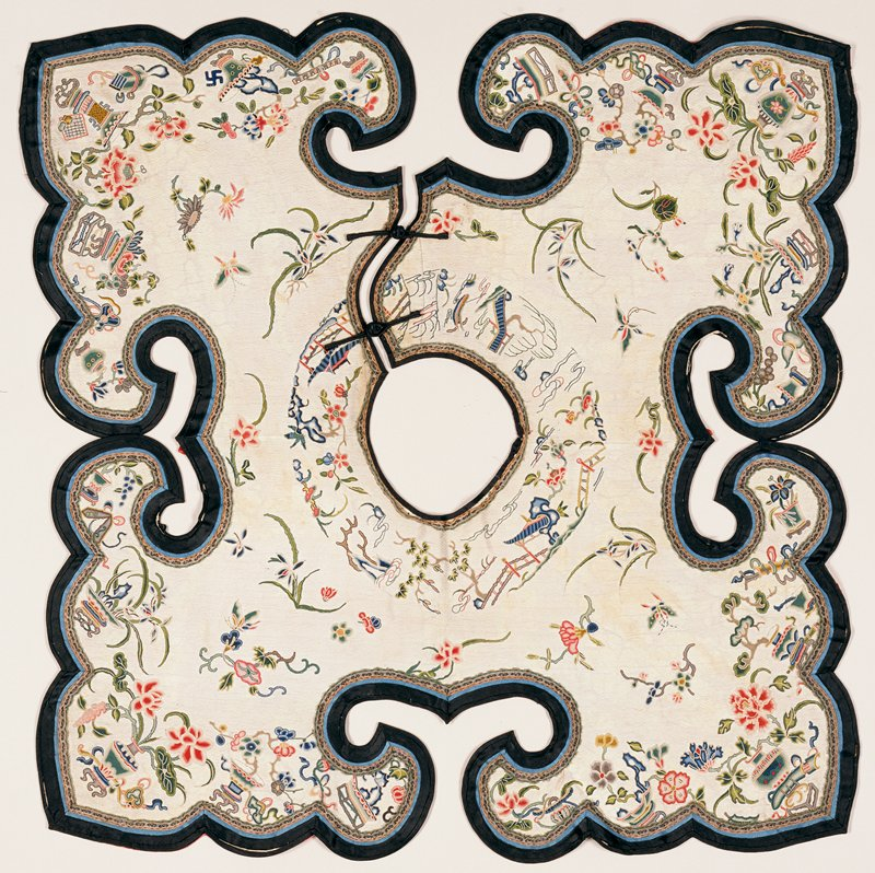 Square, shaped Collar of embroidered white brocaded silk. The design includes lotus and peony flowers and leaves, Buddhist, Daoist and other symbols, and landscape scenes, all done in the Peking Knot stitch in shades of blue, red, green, pink, yellow, brown, grey and tan. Border of black satin piped with blue. Lining of rose silk with figured ground. Soiled, and lining faded.