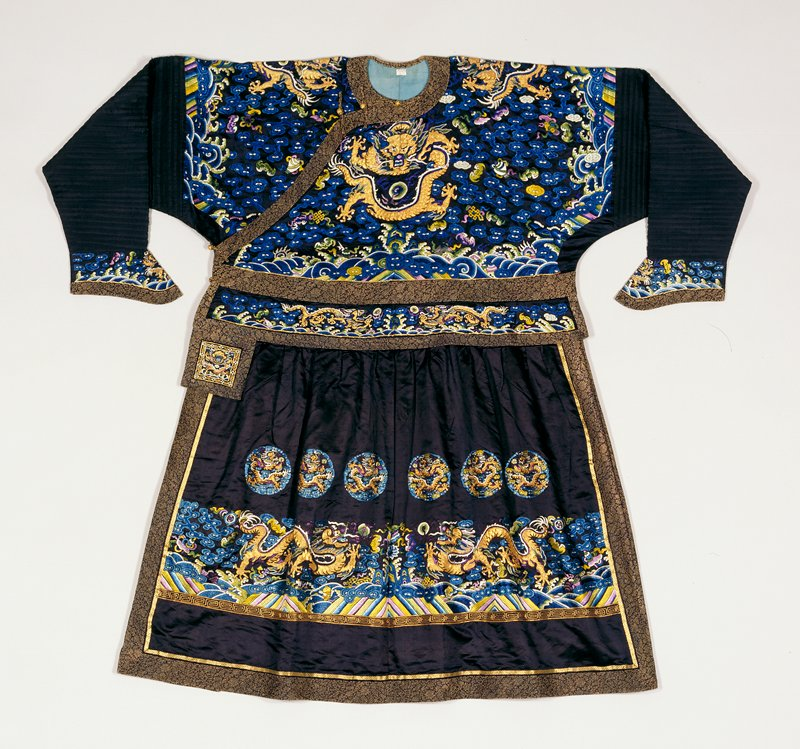 Robe of plum black satin of very large size probably designed to wear over other robes for warmth. The robe is in two sections joined at the waist, and has a very full skirt, with short tucks under a broad girdle section which hangs over skirt like a short peplum. Upper body section of robe embroidered with four large 5-clawed dragons in couched gold thread; tight clouds, bats, and Buddhist symbols in shades of blue, green, lavendar and strong violet. Beneath main dragon, front and back, the wave and sacred mountain motif usually appearing in border of robes. The peplum section, which projects into a loose tab at the opening of the robe, embroidered with horizontal dragons in gold,bats, clouds,etc. It is edged with bands of brown and gold floral brocade. The skirt embroidered, back and front with two large horizontal dragons, clouds, bats, and Buddhist emblems. Beneath is sea and earth motif. Above each dragon, three medallions (12 in all) enclosing gold dragons, clouds etc. Extremely long sleeves of corded silk. Cuffs of black, embroidered satin. Neck, front, bottom and side seams edged with bands of the brown and gold brocade. Lining of thin blue silk.