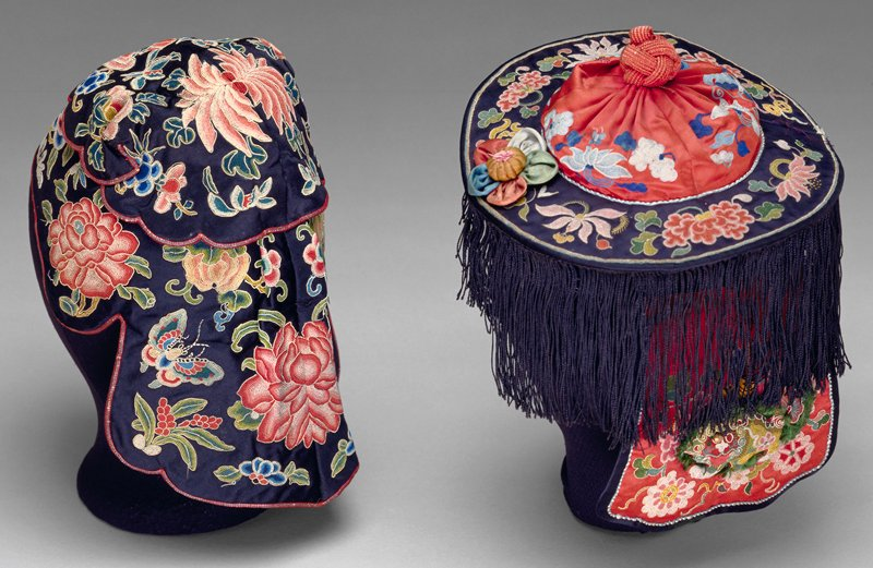 Child's hat of black satin in red and black satin embroidered in knot stitch with flowere in shades of pink, blue, green and yellow. Hat in two stafes soft crown with stiff, fringed brim and a snood to which is attached, in back, a flap of the red satin, also embroidered with flowers. Applied to brim, a paeede satin flower. Soiled. Lining of diapered blue silk.