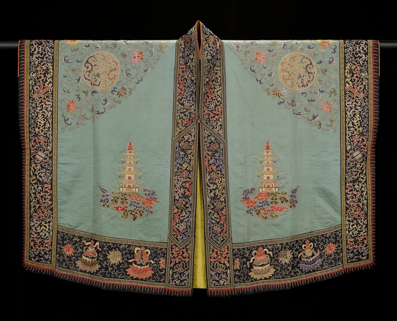 Taoist priest robe of embroidered tea-leaf green satin. On the back conventional Taoist motives, large medallions with Buddhist symbols, bats, and butterflies; lotus blossoms and good luck symbols in couched gold threads, and couched twist in colors. On the front two sacred pagodas. Borders of black satin with dragons, Buddhist and other symbols, and clouds in couched gold threads and couched twist in colors. Lining of heavy gold tribute silk of good luck symbol design.