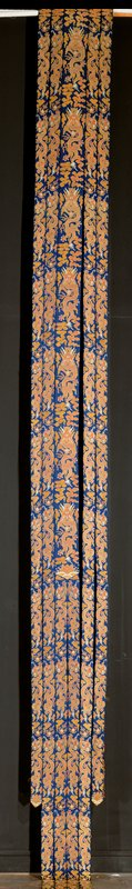 chinese imperial brocade palace hanging made up of five strips of blue satin brocaded with a continuous row of five-clawed dragons. Each strip is doubled, so that the same design appears on front and back. The wide, central strips carry the dragon full face grasping the precious jewel. Dragons on the narrower strips in profile. Scattered clouds at top and in fields; eternal sea motif at bottom.
