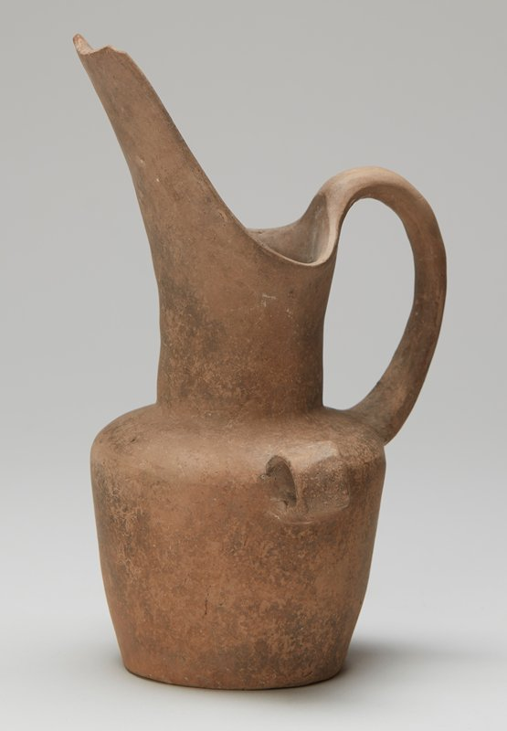 Pitcher of gray clay with deep neck and soaring spout. A graceful handle springs from the shoulders to join the rim at the back. On each side a rigin dring handle. From Nochistlan.