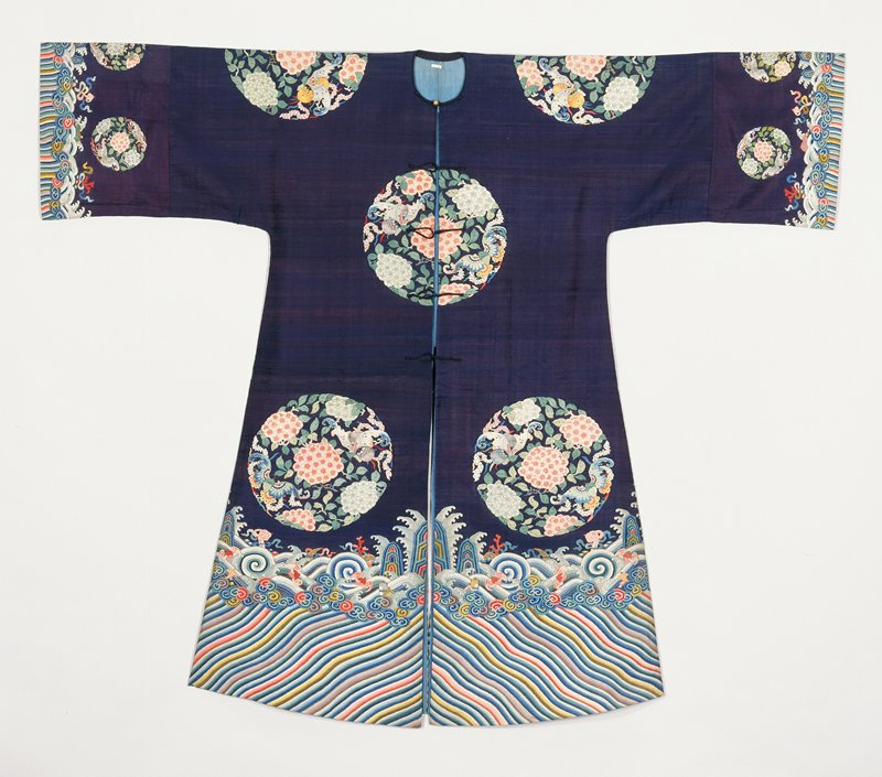 Coat of deep blue silk with a design of eight large kesi medallions containing large hydrangeas and butterflies in shades of pink, green, blue, yellow, and mauve. Conventional border of slightly wavy stripes in body colors and olive green; narrow row of tight clouds; rolling waves in which appear bats, coral, and symbols of the Eight Precious Things. Wide sleeves with border design at wrists and three small medallions of body design above. Cf. 42.8.88,91. Coat slit in back, open in front, and lined with thin blue silk.