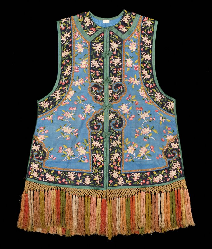 Sleeveless vest of medium blue kesi with sprays of plum blossom in red, pink, green, and purple. Border of black kesi with same design, bound all around with green satin. On the bottom a long-tassled fringe in rust, yellow, pink, and green. Lining of blue-figured silk.