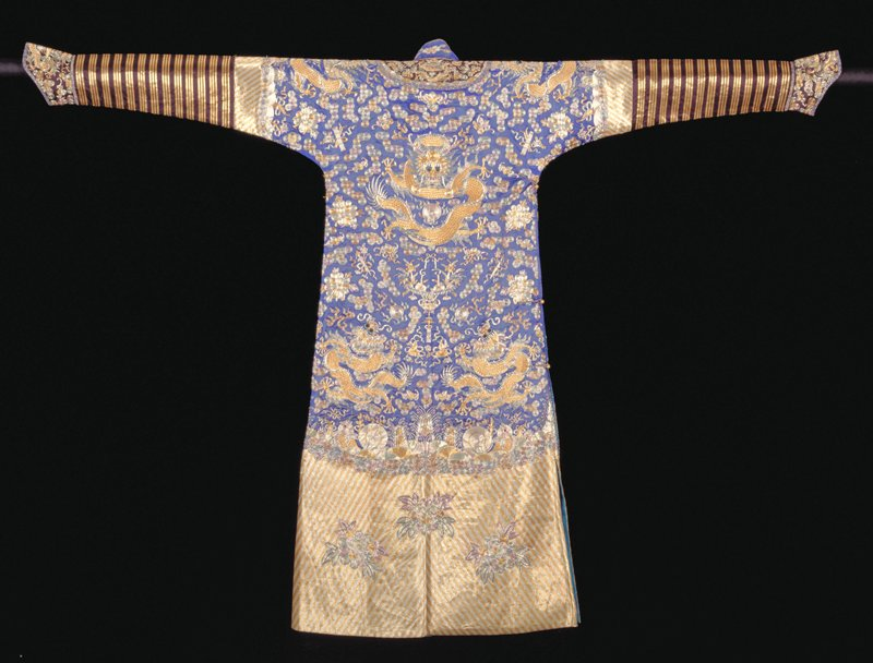 Robe of blue satin embroidered with gold and silver threads couched with colored silks; green,red, blue, black. In the field; tight clouds, bats with the swastika, peonies and Taoist symbols. Conventional border of narrow, straight slanting stripes of alternating gold and sliver threads couched respectively in red and silver. Very narrow band of pinched clouds; shallow area of rolling waves in which appear Buddhist symbols of the Eight Precious Things, all in couched gold and silver threads. In the striped area of the border are large, single peony blossoms. Below border on sleeves a strip of brown satin striped with gold threads couched in red. Cuffs and collar band of black-brown satin embroidered with couched gold and silver threads in body designs. Narrow bound edges of bright blue and gold brocade. This robe has a standing collar above collar band. Robe slit at sides and lined with thin blue silk. Cuffs lined with blue damask in dragon medallion design. Note the sheen of color conveyed by the couching in colored silks.