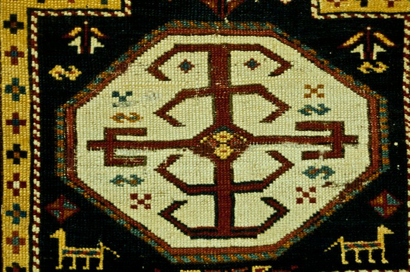 rug, long, with a blue field framed in a shaped border of yellow and red, edged with a narrow barber pole stripe, decorated with scatterd Greek crosses. In the field are six octagons in red and ivory filled with a large geometric device. Surrounding these panels are s-forms, triangular bands, animals, lozenges, and other typical Caucasian designs. Three border stripes, the central one filled with an s-shaped arrangement of the latch hook on an ivory ground, the outer and inner one carrying the barber pole stripe in red, blue, rust and white. At one end a narrow selvage with knotted warp fringe, at the other a narrow warp fringe. Sides overcast with rose-colored wool. Natural wool warp, greyish-white wool woof. Ghiordes knot. The short-cut nap of fine silky wool is worn to the warp in spots.
