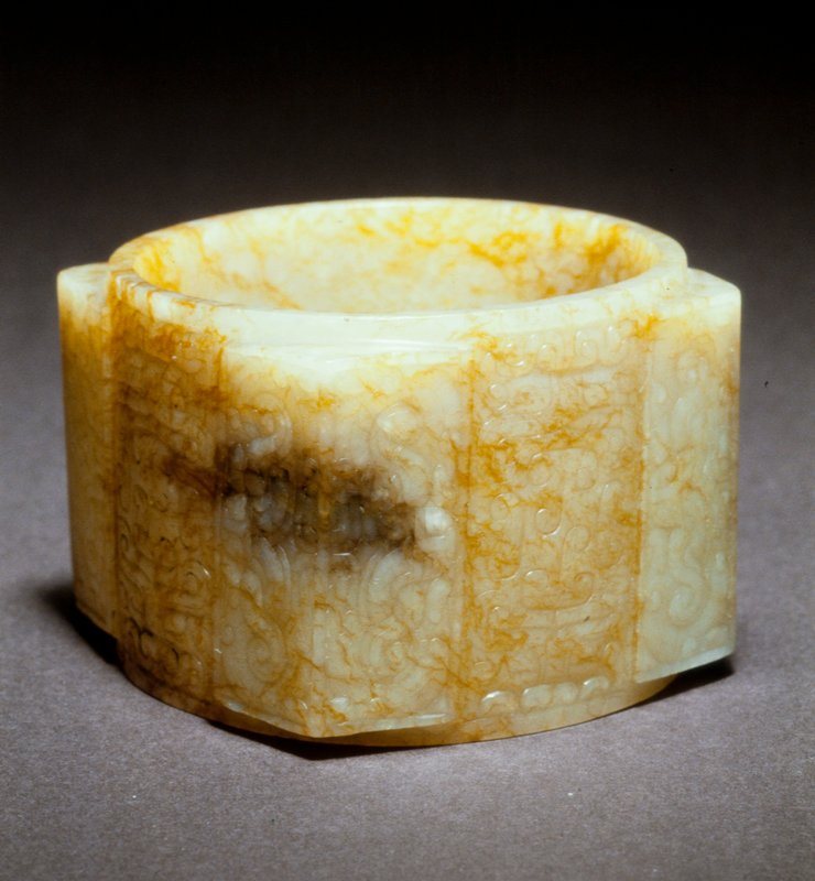 Decorative Ts'ung, translucent pale tan jade, H. 2-3/16 in., Diam. 2-3/4 in. Each of four surfaces has incised animal mask design and a poem by Chien-lung is inscribed within. 'Ceremonial piece-form of Sung broad bracelet-pale cream jade with brown cracks. [Haos ford?] Late Warring States. Probably sung with Chien Lung inscription.'