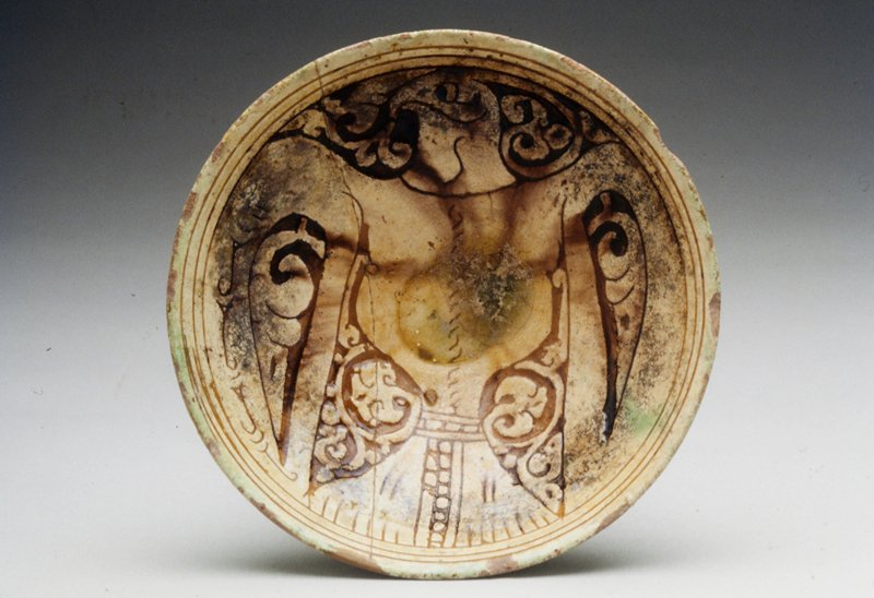 Plate beige ground, light green glaze, scratched geometric designs, H.2-1/8 in., Diam.6-3/4 in. Breaks repaired. Provincial ware from Garrus District. Slip carved ware. Red earthenware covered with white slip carved away to paste. Copper green or brownish glaze. Heraldic eagle.