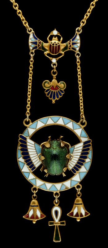pendant, metal and enamel set with green scarab within Egyptian style design and hung on chain with miniature mummy as clasp