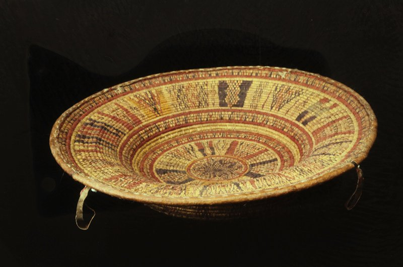 Large platter made of straw and leather; browns and red straw woven into geometric pattern; 4 leather handles evenly spaced around the rim.