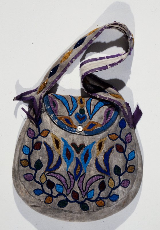 woman's shoulder bag; applique beadwork of floral pattern on leather; very small beads; button closure; edges bound in silk; L. 19 in.