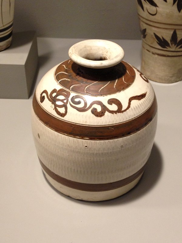 jug shaped with flat bottom; inward-flaring shoulder to narrow, short neck and flaring lip; white glaze with lightly incised pattern on body; 2 brown stripes and brown scrolling designs below a brown band with incised curves