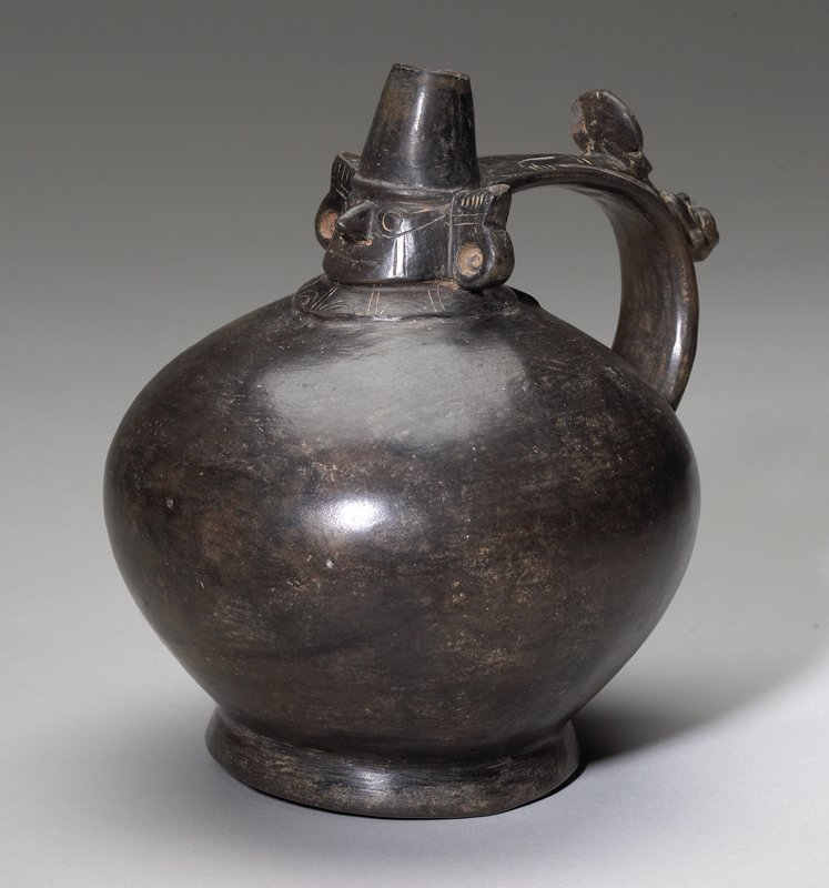 globular vessel with face of warrior/King forming the spout; handle atached to back of head has two small faces attached at midpoint; black ceramic