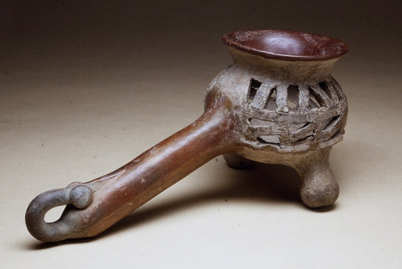 censer with two rounded feet and stylized animal head handle-end; sides perforated with tri-angular cut-outs; flare rim; burnished buff clay. Handle rattles.