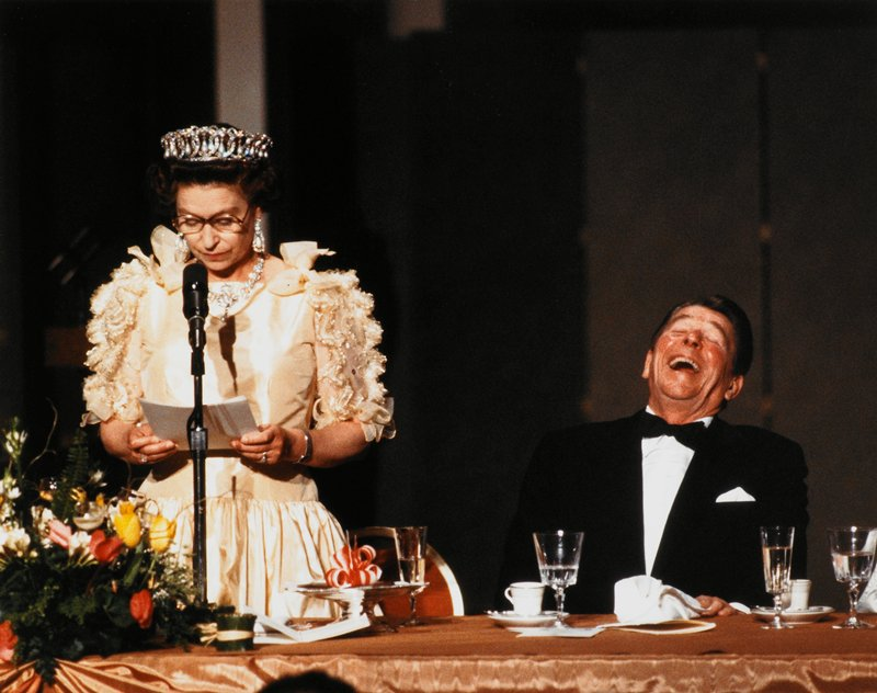 shows Queen Elizabeth II speaking at a formal dinner with Ronald Reagan seated next to her