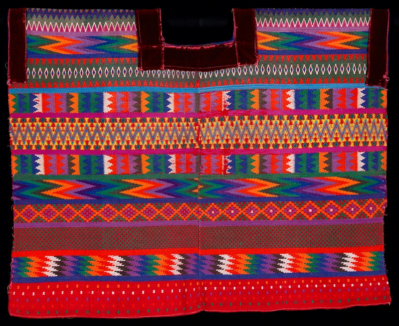two panel huipil; supplementary weft patterning on red ground cloth with applied red velvet at neck opening and armholes; geometric patterns cover entire garment, primarily diamonds, chevrons and zigzags, separated by stripes of plain weave; designs in orange, yellow, lavendar, purple green, blue.