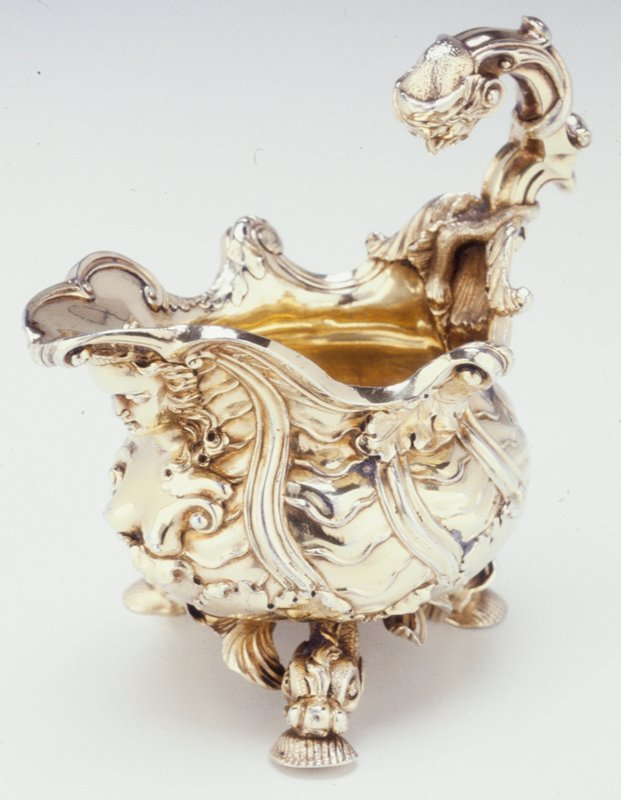 George II creamer with panels of overlapping waves; jester's head at top of handle; central scroll on rim. Later regilt