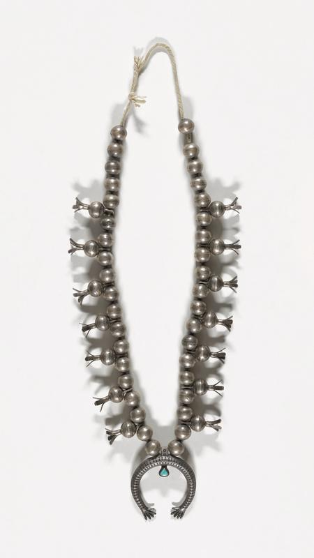Single strand of large silver beads; 14 four-pronged squash blossom beads attached to beads which have pierced extensions; 7 squash on either side of a stamped naja ending in hands, one central turquoise; tied string. J.#393, Cat.#394.