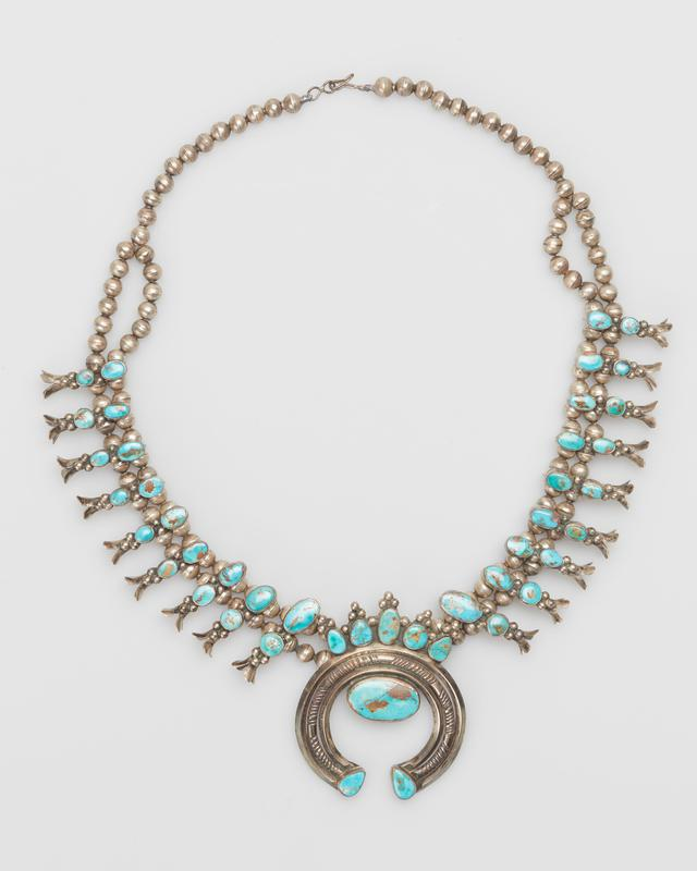 Double strand of small silver beads, single strand at 12 ends; eighteen squash blossoms, each overlaid with two irregularly shaped Blue Gem turquoises on either side of naja; triple naja of 2 carinated wires enclosing filed half-round wire, set with 8 Blue Gem turquoises of various shapes with matrix, 44 turquoise total; silver strand with silver clasp. J.#396, Cat.#490.