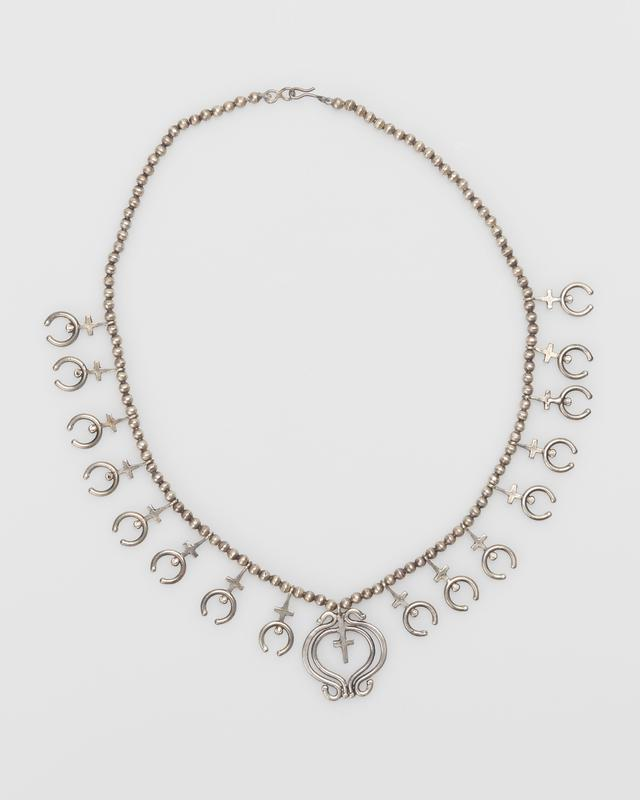 Single strand of smal spherical beads, sixteen cast silver crosses terminating in najas; cast double naja with pendant cross in center, metal strand and clip. copy of an old necklace in Smith's possession J.#442, Cat.#476.