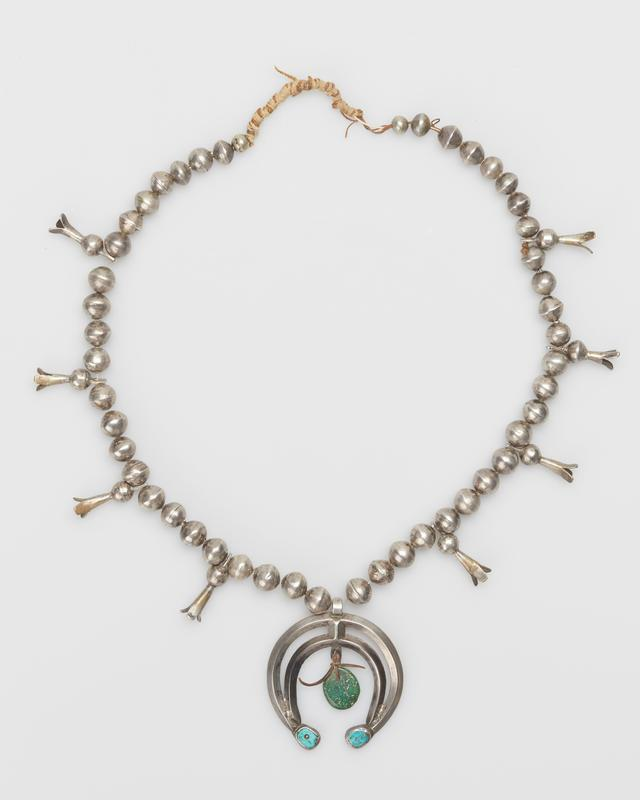 Single strand of large silver beads with 8 silver squash blossoms, 3-pronged naja double band hammered carinated naja with 2 turquoise set at terminals, and green turquoise tied with leather thong. J.#452, Cat.#371.