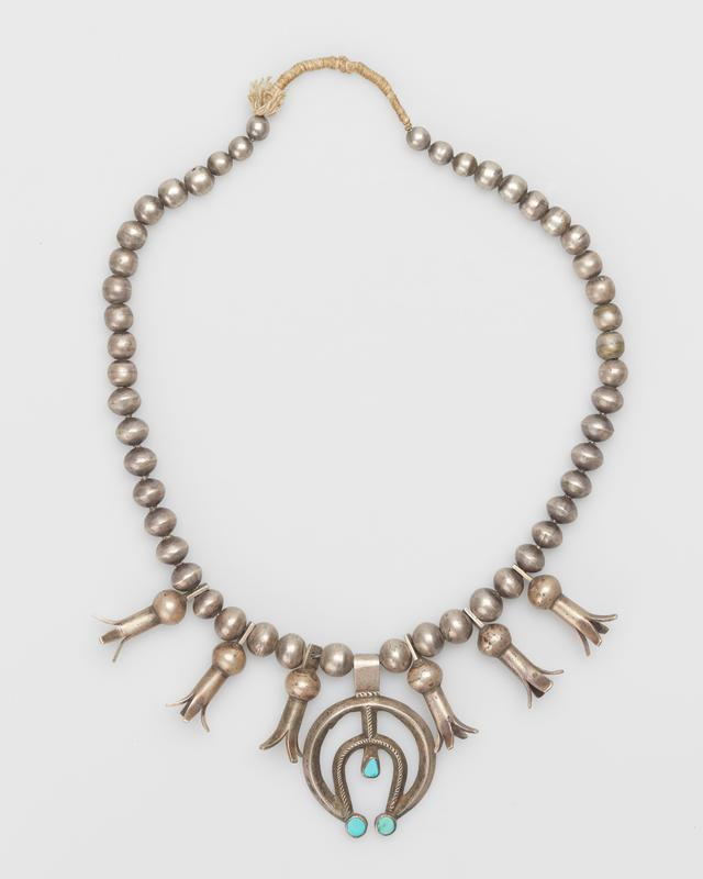 Necklace; single strand graduated silver beads; six 4-pronged squash blossoms;double-band, cast carinated filed naja; triangular turquoise at center of naja; 3 round turquoise. J# 1074, No Cat#