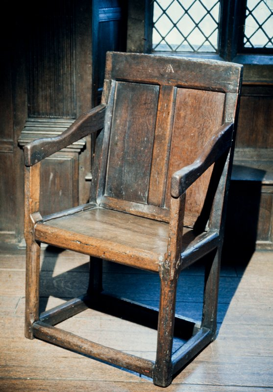 arm chair, wainscot showing simple paneling with chamfered rails. Initials(?) cut in top rail