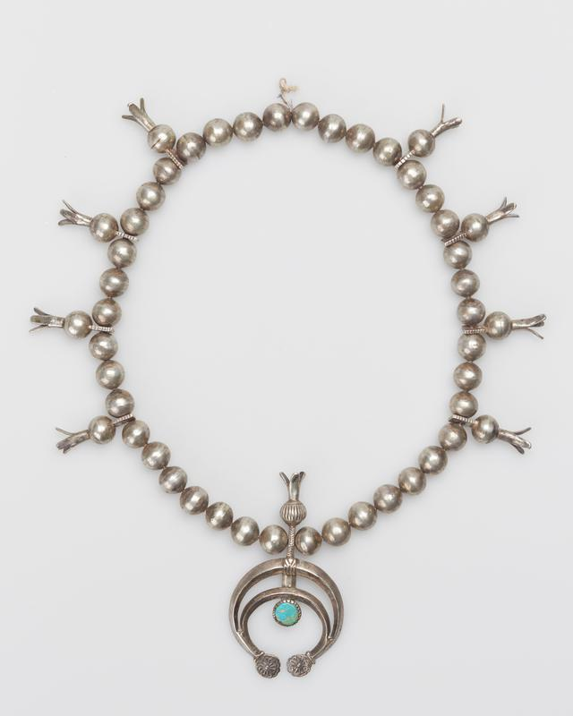 Single strand of spherical beads; eight squash blossom beads; cast double carinated naja with stamped decoration at terminals and upright squash blossom surmounting shank, round flat turquoise in serrated bezel at center J.#488, Cat.#369.