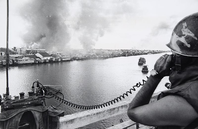 """(continuation of title) Member of the American Ninth Division speaking over radio to command post. The smoke and flames are rising from the Cholon section which has been set afire by the ARVIN troops in order to """"flush out"""" the enemy. Some fires were set by rockets fired by U.S. helicopter gunships north of the """"Y"""" Bridge on the southern side of Saigon"""