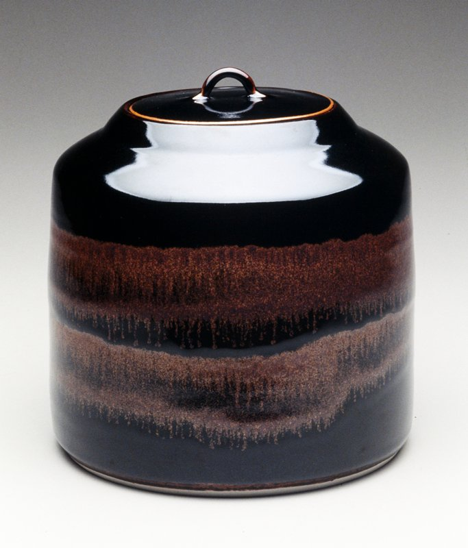 black Honan tenmoku glaze with iron wash freely applied; The iron has run in firing; two lids, one with strap handle and one with small knob