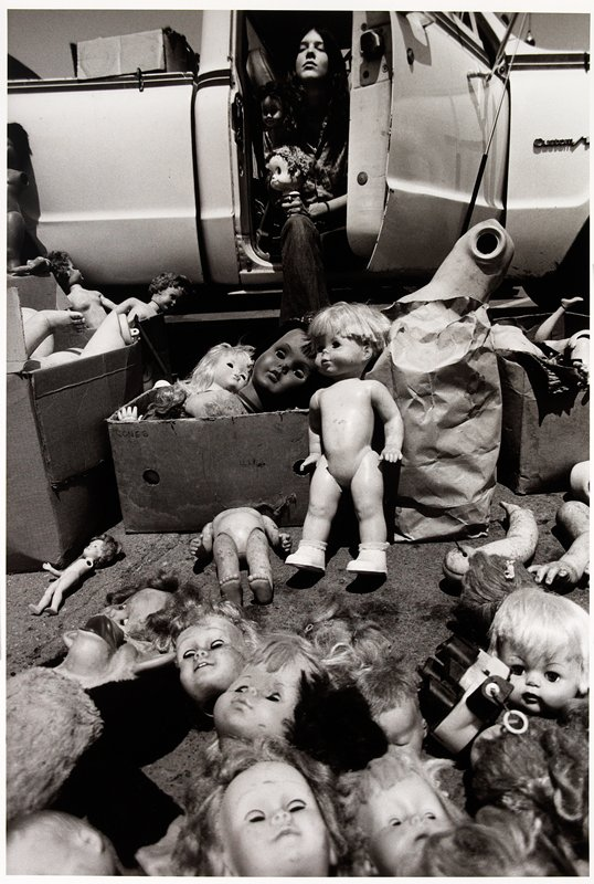 woman seated in open truck door with doll heads and body parts laid out before her