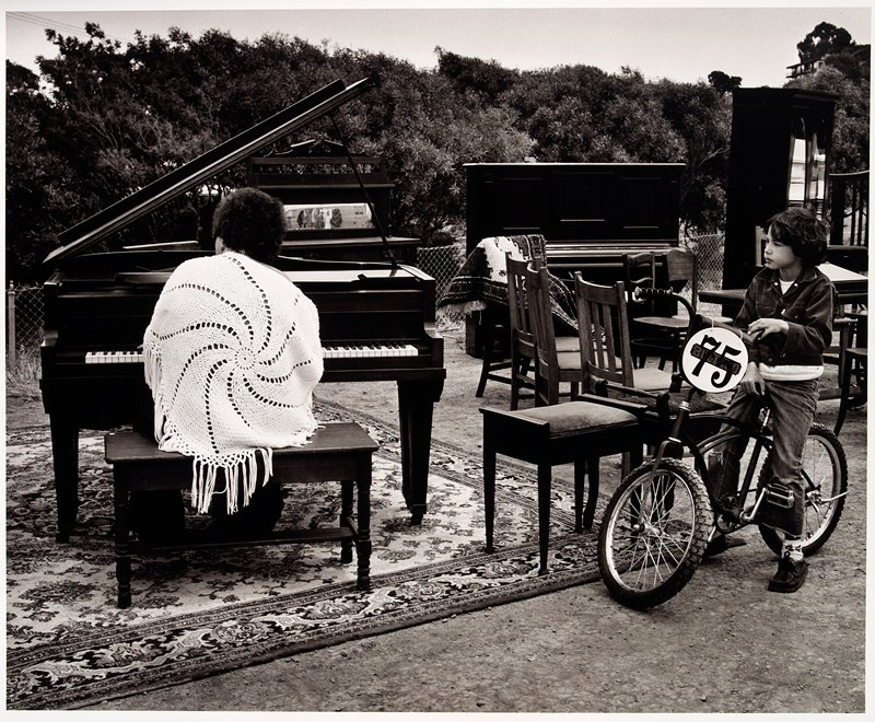 woman playing a piano while a boy seated on a bicycle looks on