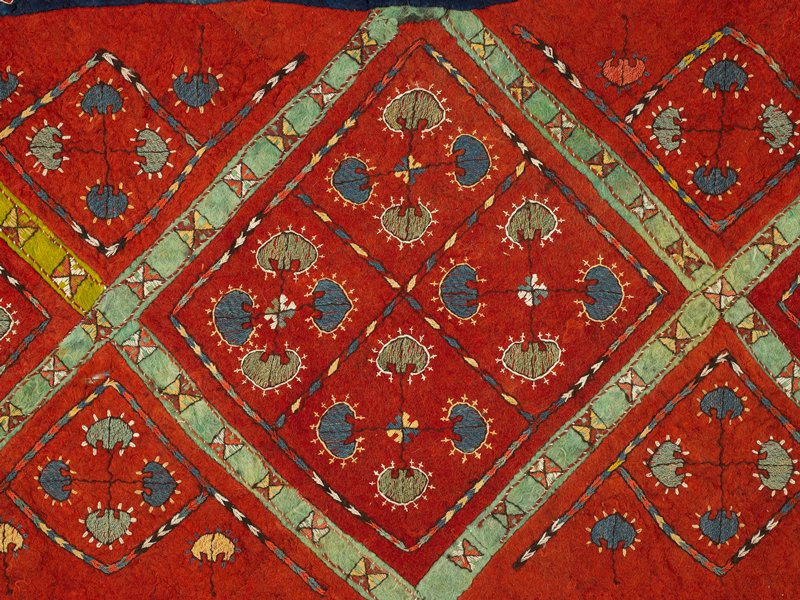 cotton applique; embroidered and applique felt rug; applied braided fringe; finger looped(?) edge; red ground with four diamond patterns across central stripe, each diamond divided into four