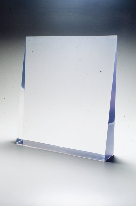 violet colored wedge shape placed on a clear acrylic pedestal base