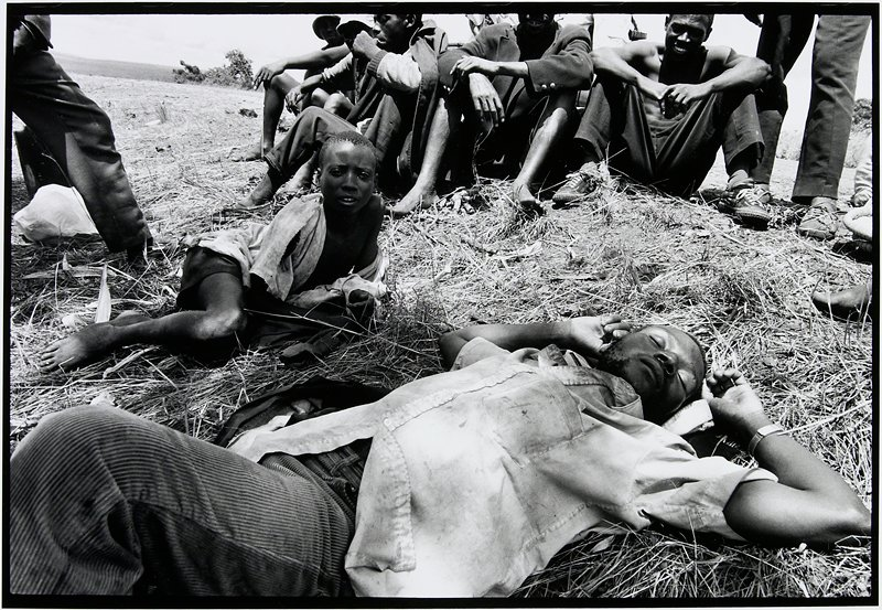 man laying on ground, child sitting beside him, group of men sitting in background