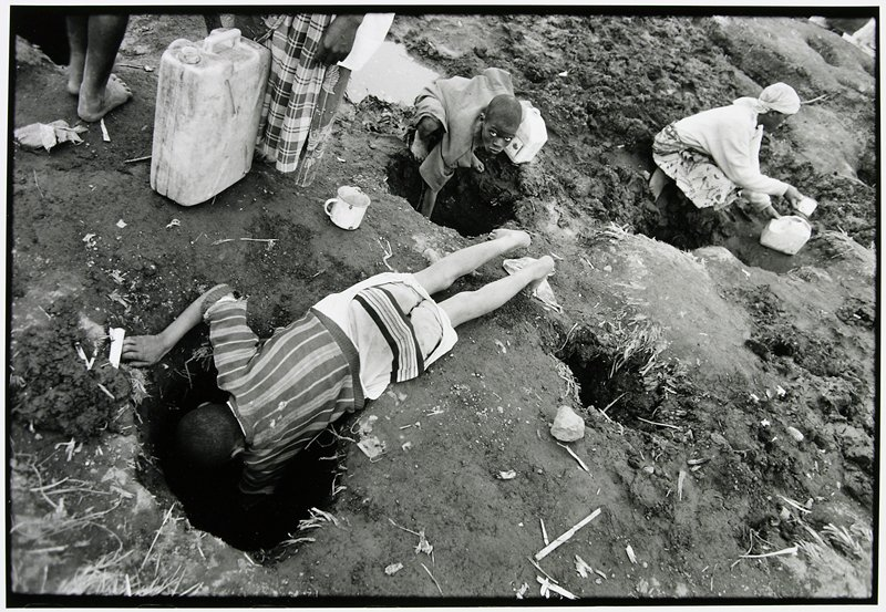 three people on the ground reaching into large holes