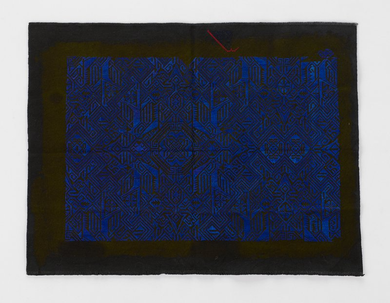 blue geometric pattern on black ground; has red and black embroidered mark on one side in margin