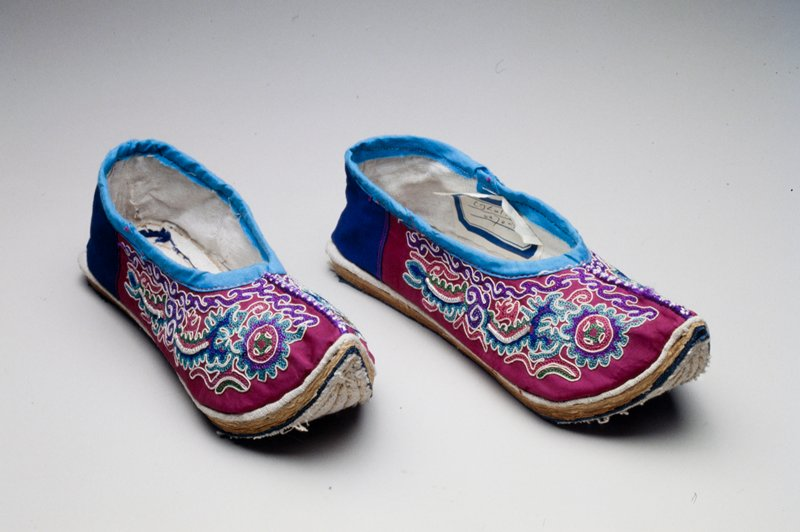 shoes with dark blue fabric in back and fuschia fabric with multicolored embroidery on sides and front; turquoise fabric trims openings for feet